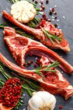 Raw lamb ribs with ingredients for cooking on dark table. Raw fresh meat, uncooked lamb ribs with ingredients for cooking. On dark table, copy space top view Royalty Free Stock Photography