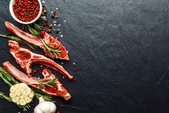 Raw lamb ribs with ingredients for cooking on dark table. Raw fresh meat, uncooked lamb ribs with ingredients for cooking. On dark table, copy space top view Royalty Free Stock Photo