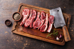Raw lamb ribs and meat cleaver. Raw fresh lamb ribs with pepper and cumin and meat cleaver on wooden cutting board on dark background royalty free stock photos