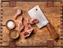 Raw lamb ribs and meat cleaver. Raw fresh lamb ribs and meat cleaver on wooden background royalty free stock photo