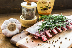 Raw lamb ribs with rosemary, pepper, garlic and oil on wooden board Stock Photo