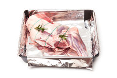 Raw lamb in roasting pan with rosemary Stock Photo