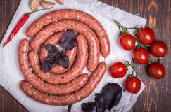 Raw lamb sausage with ingredients for salsa Royalty Free Stock Photos