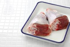 Raw lamb shank. On white butcher tray Stock Photo
