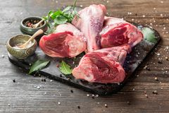 Raw lamb shanks. With salt and pepper on stone tray on rustic wooden table, selective focus Stock Photos