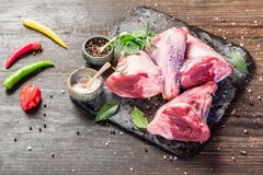 Raw lamb shanks. With salt and pepper on stone tray on rustic wooden table, selective focus Stock Image