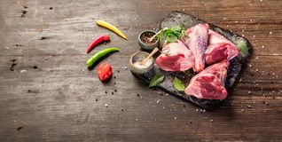 Raw lamb shanks. With salt and pepper on stone tray on rustic wooden table, selective focus Stock Photo