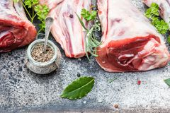 Raw lamb shanks. With salt and pepper on stone tray on rustic wooden table, selective focus Stock Photography
