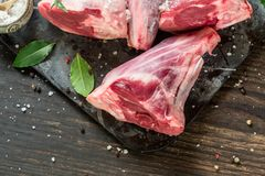 Raw lamb shanks. With salt and pepper on stone tray on rustic wooden table, selective focus Royalty Free Stock Photos
