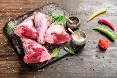 Raw lamb shanks. With salt and pepper on stone tray on rustic wooden table, selective focus Royalty Free Stock Photography