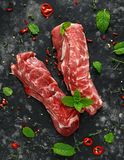 Raw lamb shoulder fillets with chilli, thyme and mint leaves Royalty Free Stock Images