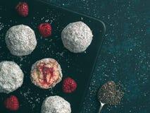 Raw lamington bliss balls with raspberries chia jam. Raw vegan lamington bliss balls with raspberries chia jam on dark background. No baked healthy vegan sweet Royalty Free Stock Images