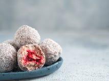 Raw lamington bliss balls with raspberries chia jam. Raw vegan lamington bliss balls with raspberries chia jam on gray background. No baked healthy vegan sweet Royalty Free Stock Photos