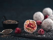 Raw lamington bliss balls with raspberries chia jam. Raw vegan lamington bliss balls with raspberries chia jam on dark background. No baked healthy vegan sweet Stock Photo