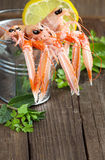 Raw langoustine in a bucket with herbs. On wood Stock Image