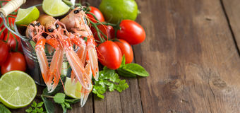 Raw langoustine in a bucket and vegetables. Raw langoustine in a bucket with vegetables and herbs on wood Stock Photos