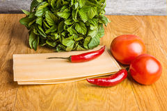 Raw lasagna with pepper and tomatoes in the cooking process Stock Images