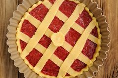 Raw lattice round cake with strawberry jam in metal form on wood Stock Photography