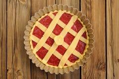 Raw lattice round cake with strawberry jam in metal form on wood Stock Photo