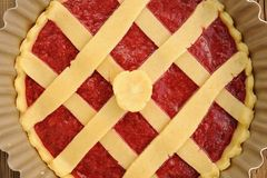 Raw lattice round cake with strawberry jam in metal form on wood Royalty Free Stock Image