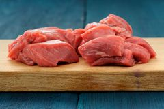 Raw lean meat cuts on wooden board on deep blue background Stock Image