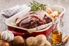 Raw leg of lamb with vegetable in a pan Stock Images