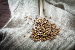 Raw lentils over spoon and woolen Stock Images