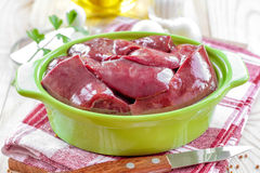Raw liver. In a bowl on a wooden table stock photo