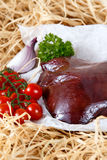 Raw liver on crumpled paper, decorated with greens and vegetables Stock Photos