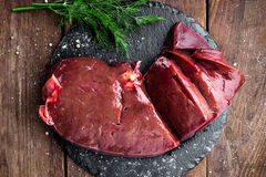 Raw liver on slate board. On wooden background top view Stock Photos