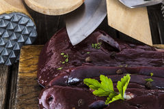 Raw liver with spices and kitchen cutlery. On a wooden surface Stock Photos