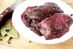 Raw liver with spices. Pieces of raw beef liver with spices Royalty Free Stock Image