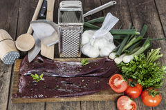 Raw liver and vegetables with kitchenware Stock Photo