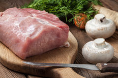 Raw loin on a chopping board. Prepare a meal of pork and vegetables Royalty Free Stock Images