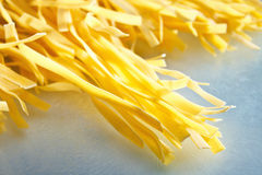 Raw, long tagliatelle pasta Stock Image