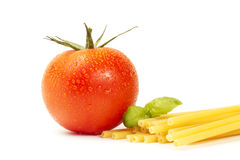 Raw macaroni with basil and tomato Stock Photography