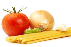 Raw macaroni with basil, wet tomato, onion and gar. Lic clove on white background Stock Photos