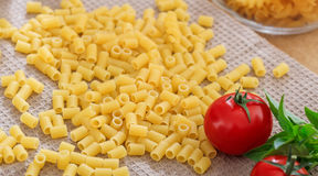 Raw macaroni pasta with tomatoes. And basil Royalty Free Stock Photos