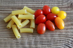 Raw Maccharoni Pasta with Cherry Tomatoes on wooden table Royalty Free Stock Images