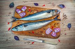 Raw mackerel fish on a wooden cutting board with spices. – red onion, basil leaves, chili peppers and peppercorn Stock Photos