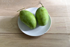 Raw mangoes on white dish. And wood background Royalty Free Stock Images