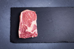 Raw marble, fresh piece of meat, black Angus ribeye steak on a dark stone background. Royalty Free Stock Images