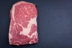Raw marble, fresh piece of meat, black Angus ribeye steak on a dark stone background. Stock Photo