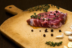 Raw marbled beef on a cutting board. On a black background Royalty Free Stock Photos