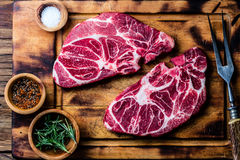 Raw marbled beef steaks on wooden cutting board. Top view Royalty Free Stock Images