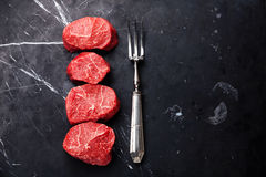 Raw marbled meat Steak filet mignon and meat fork. Raw fresh marbled meat Steak filet mignon and meat fork on dark marble background Royalty Free Stock Image
