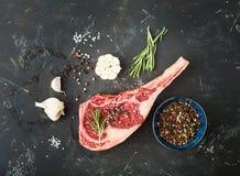 Raw marbled meat steak. Herbs, seasonings, garlic, rustic stone background. Beef Rib eye steak on bone, ready for cooking. Top view. Ingredients for meat stock photo