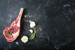 Raw marbled meat steak. Herbs, seasonings, rustic stone background. Space for text. Beef Rib eye steak on bone, ready for cooking. Top view. Copy space stock photography