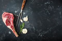 Raw marbled meat steak. Fork, seasonings, rustic stone background. Space for text. Beef Rib eye steak on bone, ready for cooking. Top view. Copy space stock photo