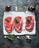Raw marbled  Steaks on white paper with coking ingredients. Top view Royalty Free Stock Photo